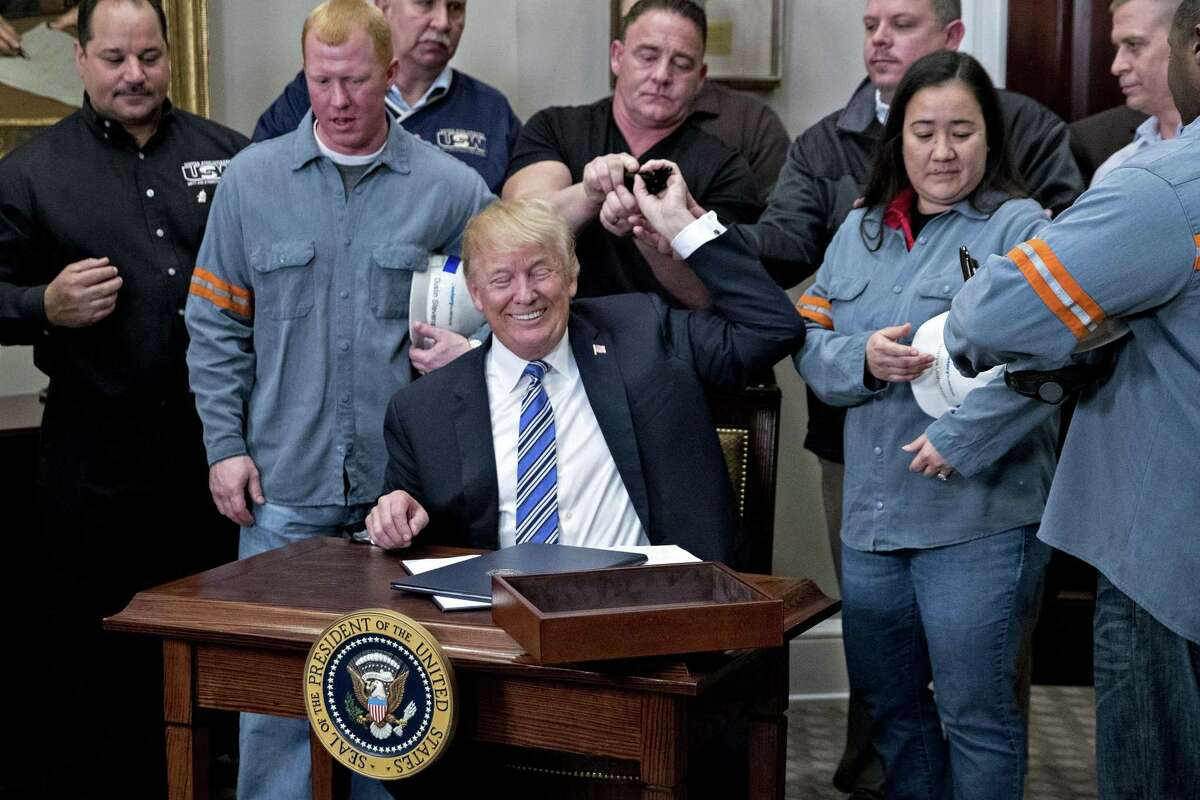 U.S. President Donald Trump hands pens to steel and aluminum workers after signing proclamations on adjusting imports of steel and aluminum into the United States next to in the Roosevelt Room of the White House in Washington, D.C., U.S., on Thursday, March 8, 2018. Trump signed the order over steel and aluminum tariffs that he said could spare certain countries if they have strong trading and military ties with the U.S. telling reporters earlier that Mexico and Canada would likely not face the levies if they renegotiate the North American Free Trade Agreement. Photographer: Andrew Harrer/Bloomberg
