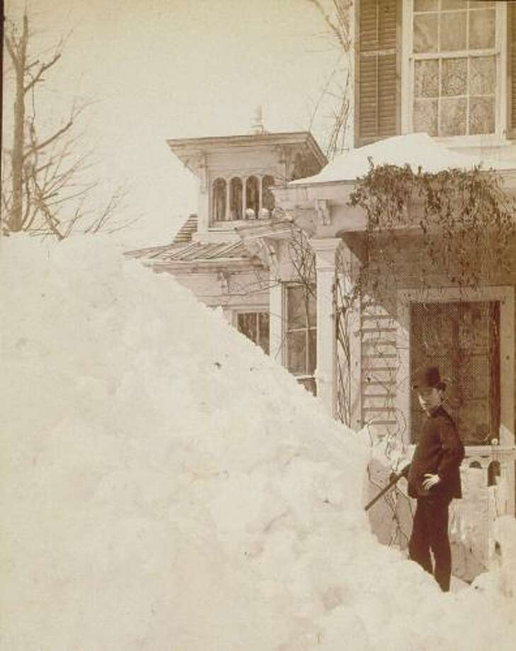 A young man stands beside a large pile of snow at 380 Main St., Danbury, after the Blizzard of 1888, which started on March 12. Photo: /Connecticut Digital Archive
