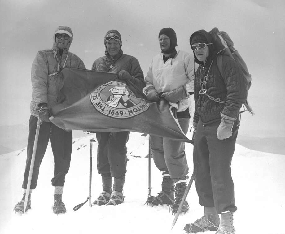Image shows Governor Evans and three members of his staff atop Mt. Rainier holding a Washington State flag, July 21, 1965. Photo: Washington State Archives