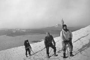 Image shows Governor Dan Evans, Frank Pritchard, Jr. and George Senner as they climb Mount Rainier. Bill Bell likely took the photograph. As they climb the slope, Mount Adams rises in the distance to the south. 1965.
