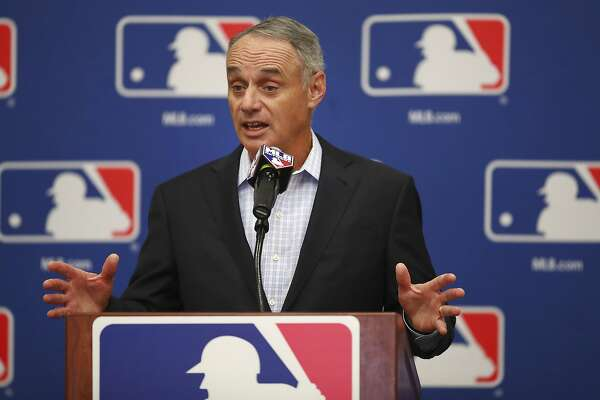 FILE - In this Feb. 20, 2018, file photo, Major League Baseball Commissioner Rob Manfred gestures while speaking at an owners meeting in Glendale, Ariz. Facebook is getting deeper into the professional sports streaming game, signing a deal with Major League Baseball to show 25 afternoon games in an exclusive deal. The games will be available Facebook users in the U.S. on Facebook Watch, the company�s video feature, via the MLB Live show page Facebook said Friday, March 9. (AP Photo/Ben Margot, File)
