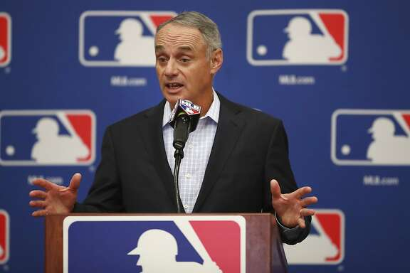 FILE - In this Feb. 20, 2018, file photo, Major League Baseball Commissioner Rob Manfred gestures while speaking at an owners meeting in Glendale, Ariz. Facebook is getting deeper into the professional sports streaming game, signing a deal with Major League Baseball to show 25 afternoon games in an exclusive deal. The games will be available Facebook users in the U.S. on Facebook Watch, the company's video feature, via the MLB Live show page Facebook said Friday, March 9. (AP Photo/Ben Margot, File)