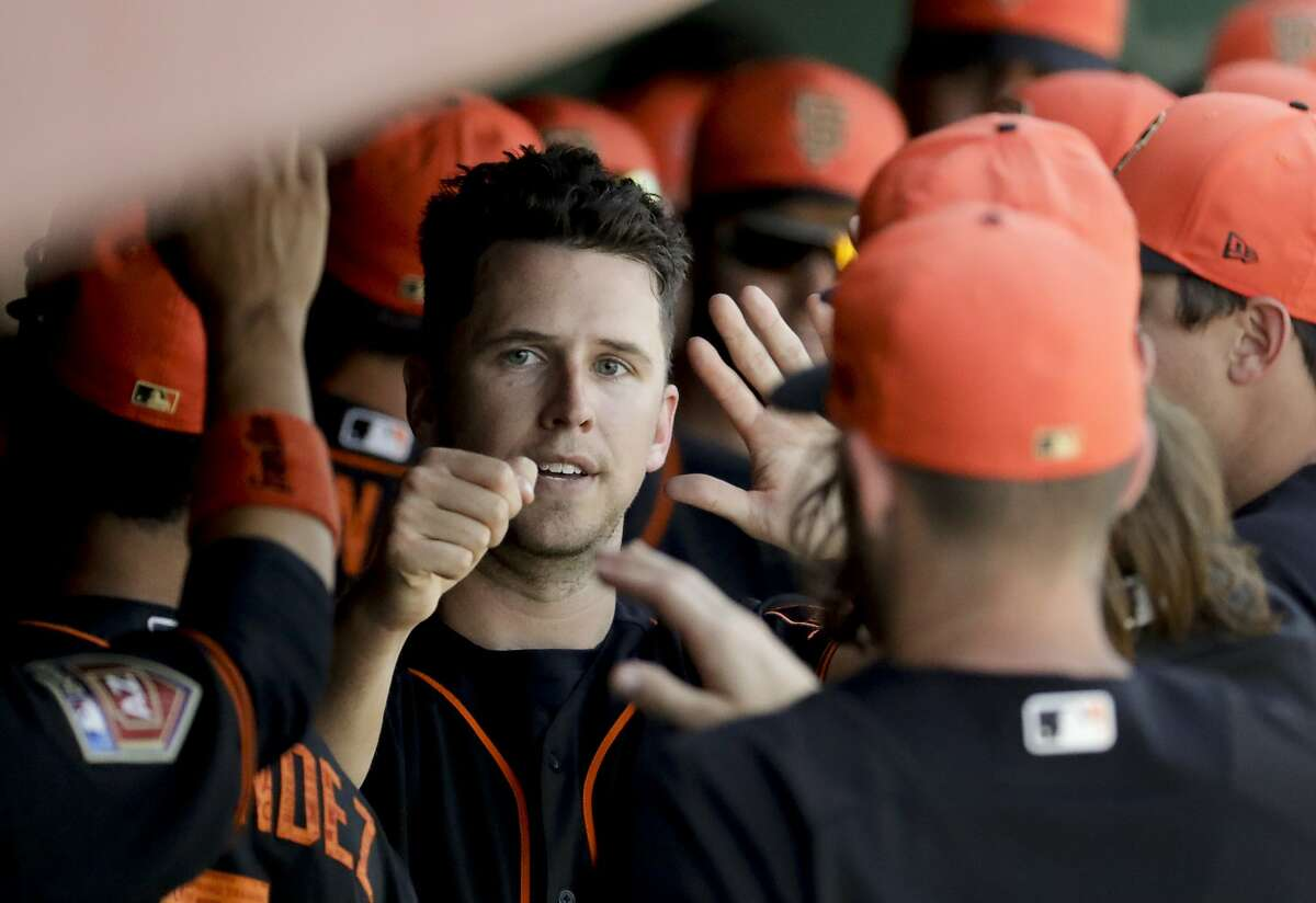 San Francisco Giants' Buster Posey celebrates in the dugout after scoring on a single by Pablo Sandoval during the fourth inning of a spring baseball game against the Seattle Mariners in Scottsdale, Ariz., Friday, March 9, 2018. (AP Photo/Chris Carlson)