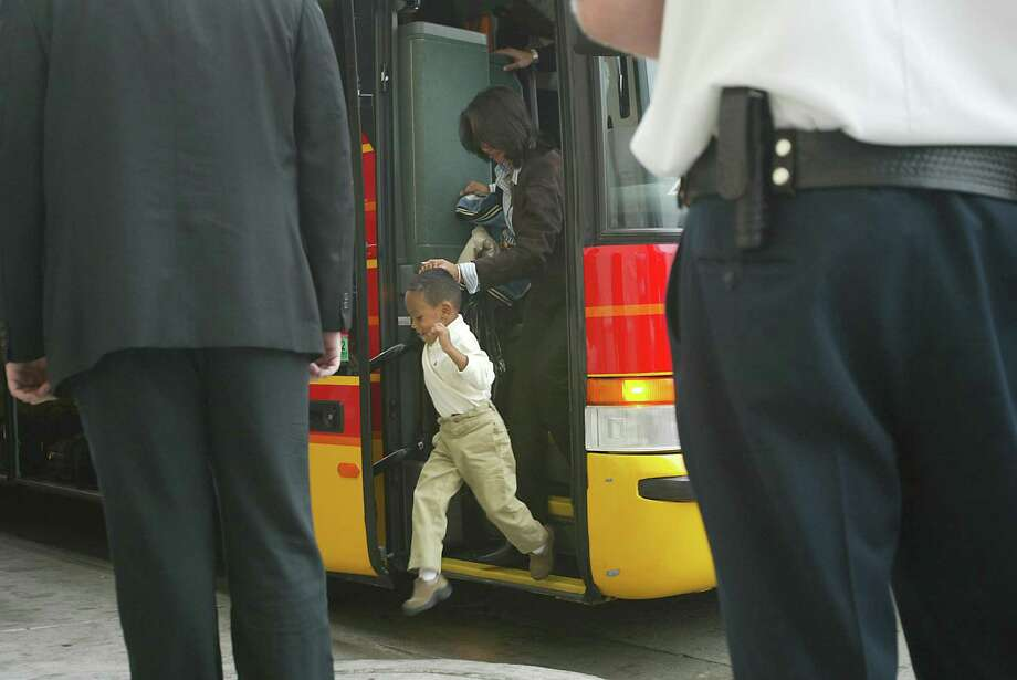 A hand held by a loving mother can say home and safety to a child. Here, Darren Baker, 3, son of San Francisco Giants' manager Dusty Baker, jumps off the big step of the team bus in 2002. Photo: DEANNE FITZMAURICE /SFC / CHRONICLE