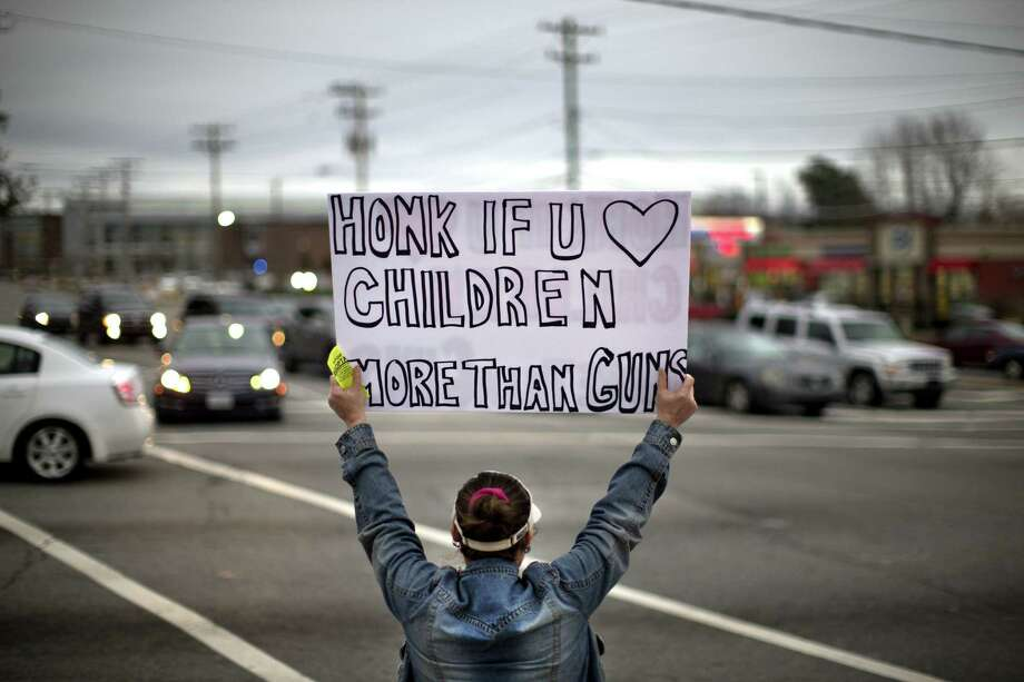 Megan Longstreet holds up a sign as she stands in solidarity with victims of the Marjory Stoneman Douglas High School shooting Feb. 28 in Greensboro, N.C. Photo: Andrew Krech /Associated Press / News & Record