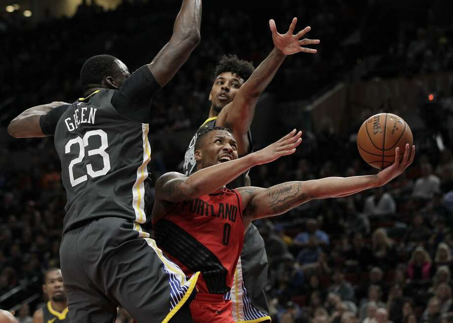 Portland Trail Blazers guard Damian Lillard, center, drives to the basket against Golden State Warriors forward Draymond Green, left, and guard Nick Young during the second half of an NBA basketball game in Portland, Ore., Wednesday, Feb. 14, 2018. The Trail Blazers won 123-117. (AP Photo/Steve Dipaola) Photo: Steve Dipaola, Associated Press