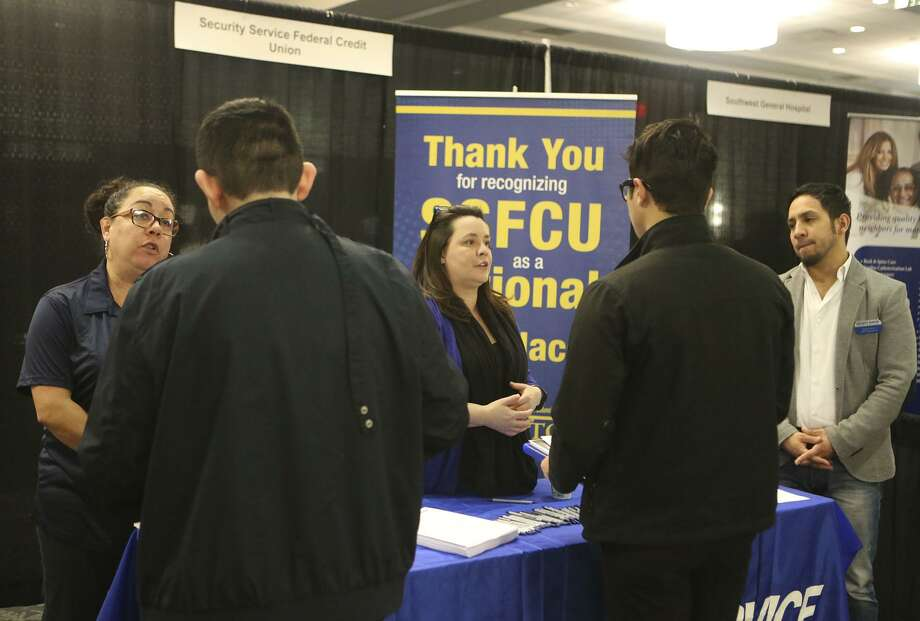 Valerie Siller (left, facing) Melissa Medley (center, facing) and Adrian Torres (right, facing) answer questions about employment opportunities at Security Service Federal Credit Union during a Mega Career Fair at the Norris Conference Center on Loop 410. Photo: John Davenport /San Antonio Express-News / ©John Davenport/San Antonio Express-News