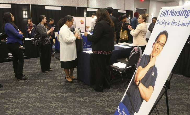 People ask questions about employment opportunities at University Health System Wednesday February 21, 2018 during the Mega Career Fair at the Norris Conference Center on Loop 410. Twenty six companies were represented at the event offering employment in manufacturing, transportation, healthcare and more.