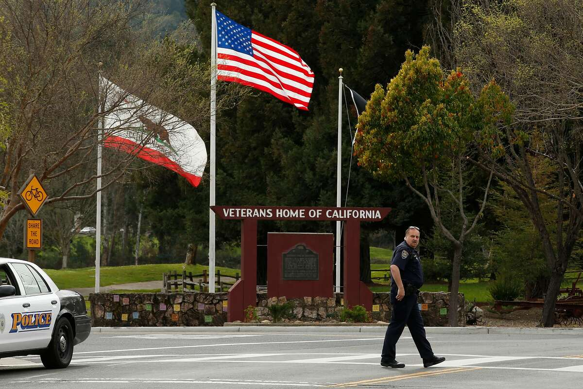 Jeff Hullquist, the Chief of Police of the Napa Valley Railroad Police Department, stands guard and leads motorists away from the Veterans Home of California during an ongoing hostage situation, Friday, March 9, 2018, in Yountville, Calif.