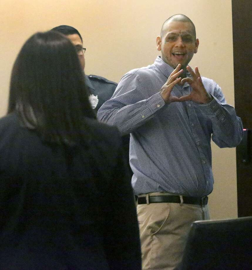 "Gabriel Moreno, accused with two others of killing Jose Luis Menchaca, gives a ""heart"" sign Friday in the 379th state District Court after a mistrial was declared by Judge Ron Rangel. Menchaca was dismembered and his remains were grilled on a barbecue pit for what witnesses said was retaliation for a bad drug deal. Photo: John Davenport /San Antonio Express-News / ©John Davenport/San Antonio Express-News"