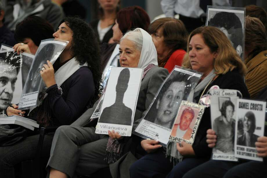 Protesters hold images of disappeared people during the 2010 sentencing in Buenos Aires of Reynaldo Bignone, Argentina's last military dictator. Photo: Rolando Andrade Stracuzzi, AP