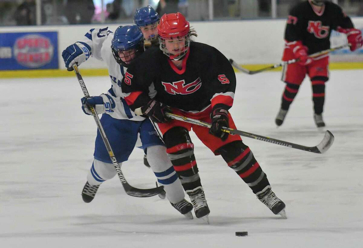 Anika Curri (5) of the New Canaan Rams brings the puck up ice during the state semi-final game against the Darien Blue Wave at the Shelton Rinks on Friday March 9, 2018, in Shelton, Connecticut.