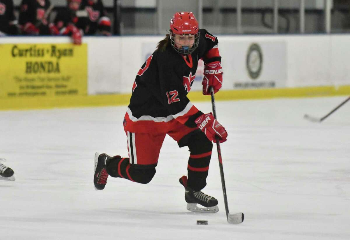 Elizabeth McCarthy (12) of the New Canaan Rams brings the puck across center ice during the state semi-final game against the Darien Blue Wave at the Shelton Rinks on Friday March 9, 2018, in Shelton, Connecticut.