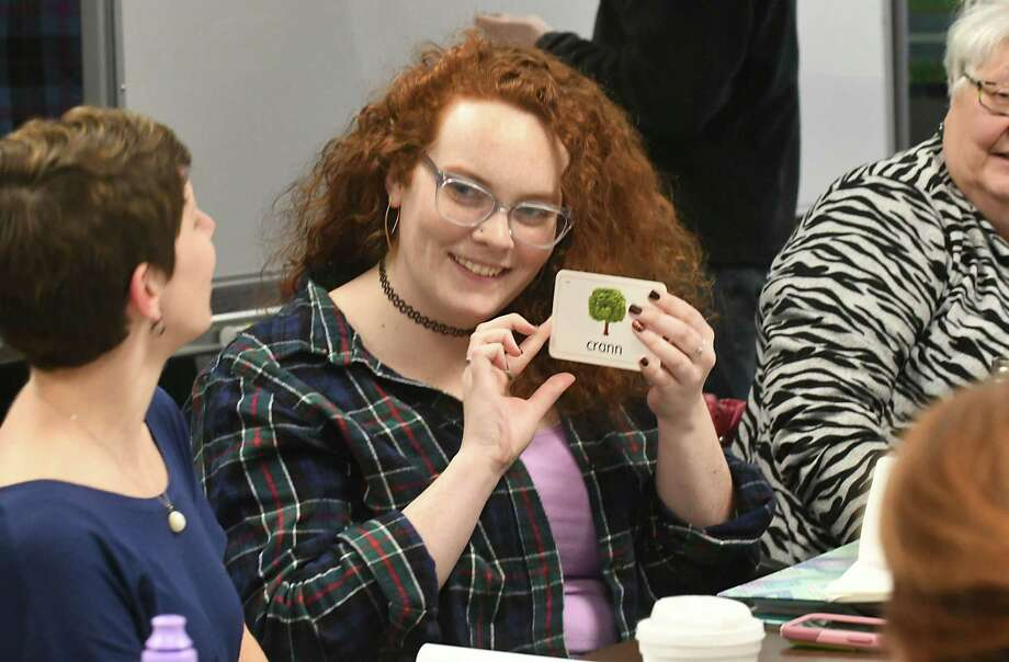 Brigid Munafo of Albany holds up a flash card of a tree for the person sitting next to her during an exercise in an Irish Gaelic Language class at the Celtic Hall on Thursday, March 8, 2018 in Colonie, N.Y. The program is certified by the Irish government. (Lori Van Buren/Times Union) Photo: Lori Van Buren, Albany Times Union / 20043165A