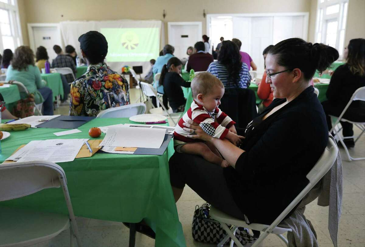 Lisa Richardson with her 4-month-old son attend a February workshop hosted by RAICES and their shelter program organization Casa de Raices for people interested in learning how to assist and advise refugees, especially women and their children, placed in family detention.