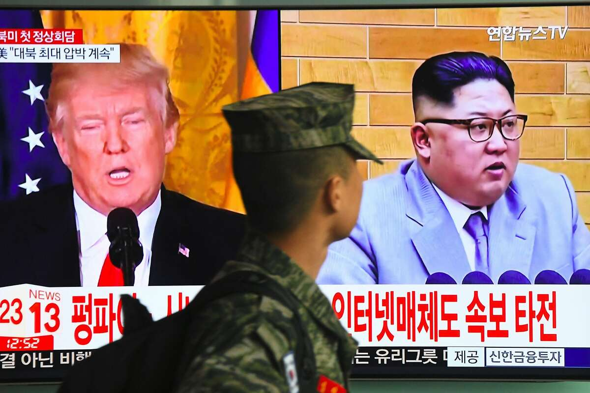 TOPSHOT - A South Korean soldier walks past a television screen showing pictures of US President Donald Trump (L) and North Korean leader Kim Jong Un at a railway station in Seoul on March 9, 2018. US President Donald Trump agreed on March 8 to a historic first meeting with North Korean leader Kim Jong Un in a stunning development in America's high-stakes nuclear standoff with North Korea. / AFP PHOTO / Jung Yeon-jeJUNG YEON-JE/AFP/Getty Images