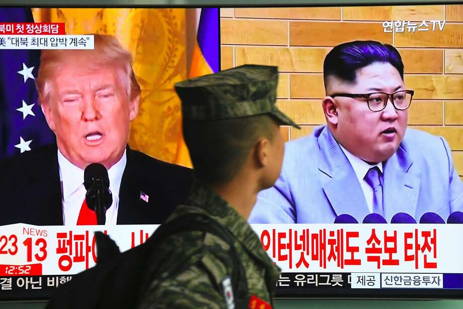 TOPSHOT - A South Korean soldier walks past a television screen showing pictures of US President Donald Trump (L) and North Korean leader Kim Jong Un at a railway station in Seoul on March 9, 2018.  US President Donald Trump agreed on March 8 to a historic first meeting with North Korean leader Kim Jong Un in a stunning development in America's high-stakes nuclear standoff with North Korea. / AFP PHOTO / Jung Yeon-jeJUNG YEON-JE/AFP/Getty Images Photo: JUNG YEON-JE, AFP/Getty Images