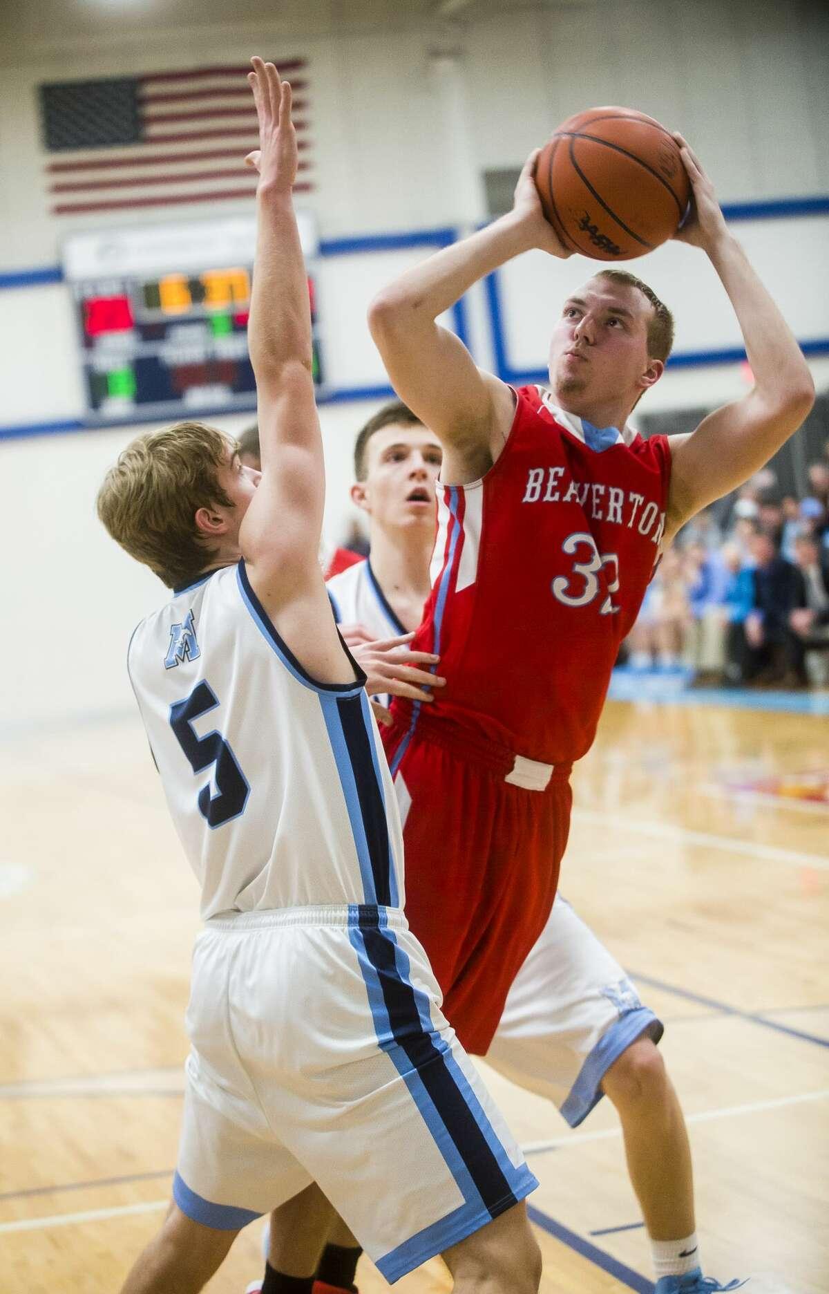 Beaverton junior Logan Gerow takes a shot while Meridian senior Garrett Stockford guards him during their district championship game on Friday, March 9, 2018 at Meridian High School. (Katy Kildee/kkildee@mdn.net)