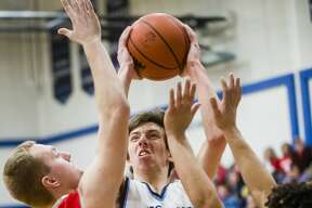 Meridian senior Hunter Wishowski takes a shot while Beaverton junior Logan Gerow, left, and senior Nate Taylor, right, guard him during their district championship game on Friday, March 9, 2018 at Meridian High School. (Katy Kildee/kkildee@mdn.net)