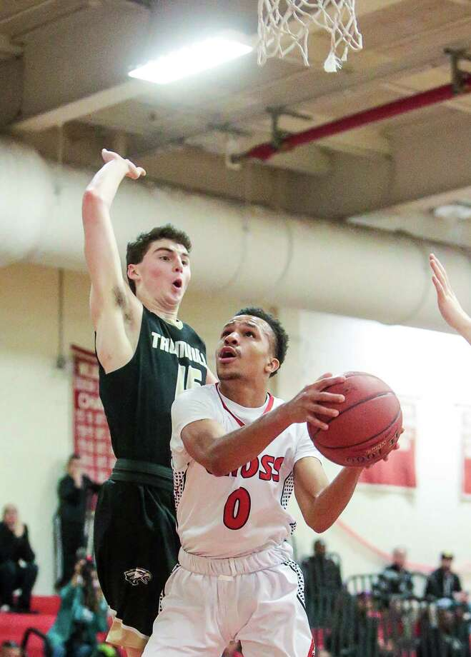 Cross's Kwane Taylor goes up for layup on Trumbull defender Chris Brown during the Governor's 67-65 win Friday night in New Haven. Photo: John Vanacore / For Hearst Connecticut Media
