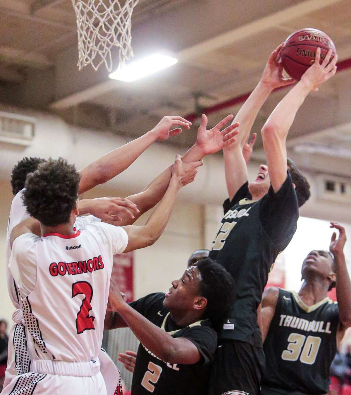 Trumbull's John Paul Fromageot (22) battles for an offensive rebound during their 67-65 loss to Wilbur Cross Friday evening in New Haven.