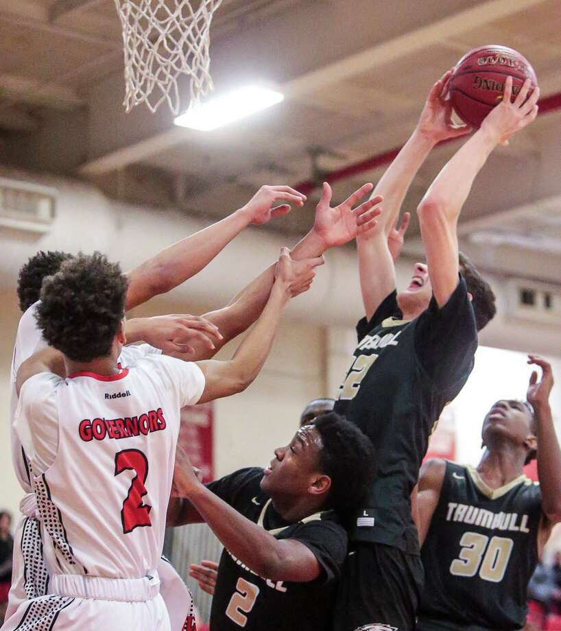 Trumbull's John Paul Fromageot (22) battles for an offensive rebound during their 67-65 loss to Wilbur Cross Friday evening in New Haven. Photo: John Vanacore / For Hearst Connecticut Media