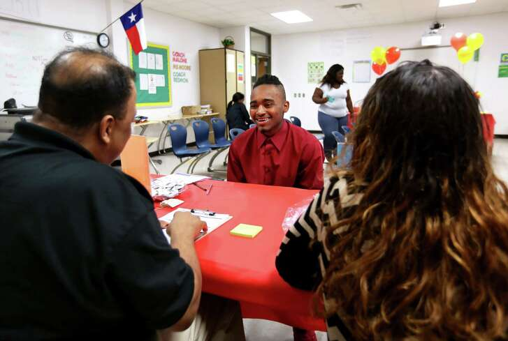 A job candidate, center, smiles during his interview with McDonalds' staff during a Hire Houston Youth job fair at Worthing High School on April 29, 2017.