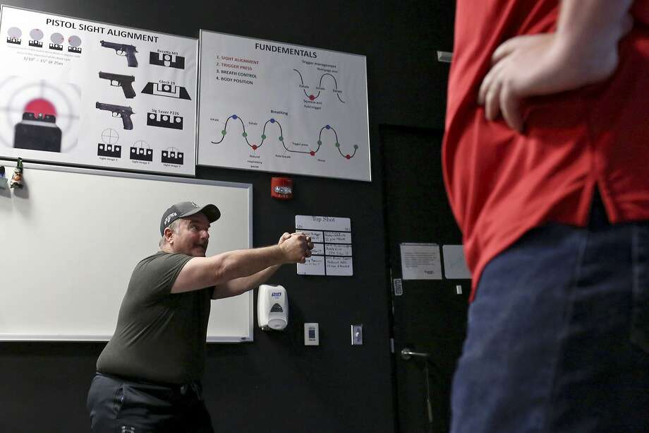 Sutherland Springs survivor David Colbath (left) talks about shooting with his left hand after going through an active shooter simulation with the help of instructor Scott Fitzgerald at the Center for the Intrepid. Photo: Photos By Lisa Krantz / San Antonio Express-News / SAN ANTONIO EXPRESS-NEWS