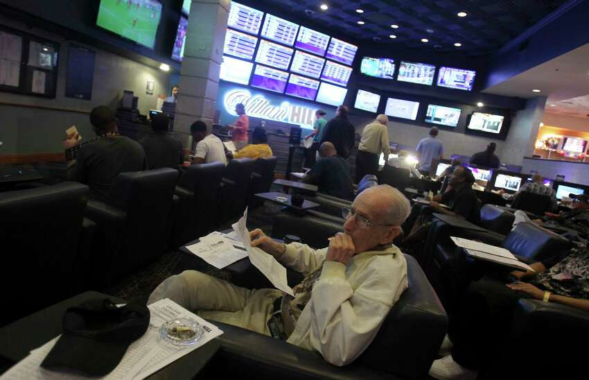 Al Smith smokes a cigarette inside the race and sports book room of the Silver Sevens Hotel and Casino in Las Vegas, Nov. 14, 2014. Pro sports leagues often play down their formal opposition to organized gambling, but NBA Commissioner Adam Silver went much further on Friday, calling for federal law to allow betting on games. (Isaac Brekken/The New York Times) ORG XMIT: XNYT110