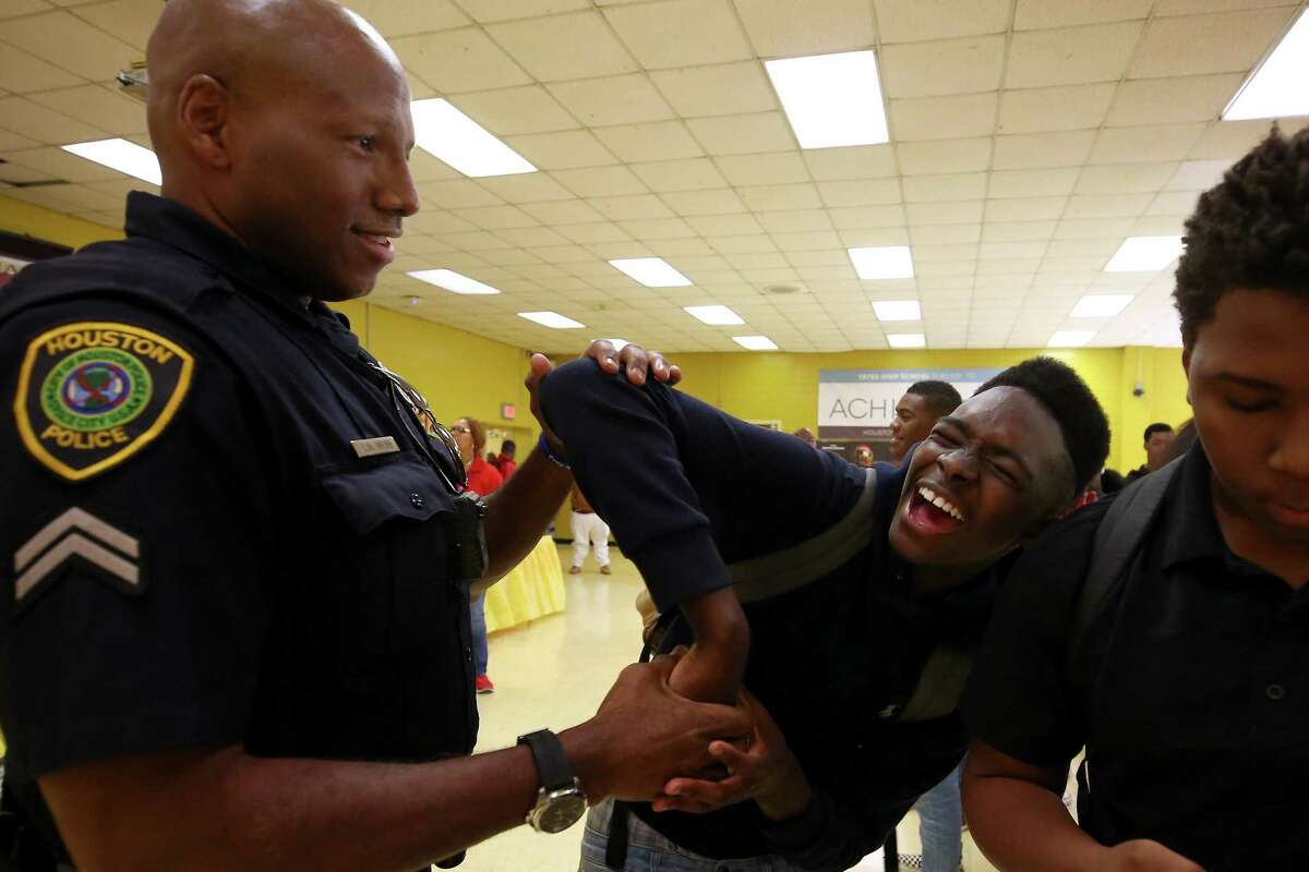 Houston Police officer Charles Webb, left, shows Jack Yates High School student Jakobi Morrison Jacobs an arresting technique during a One Houston, One Hood initiative lunch Friday, March 9, 2018, in Houston.