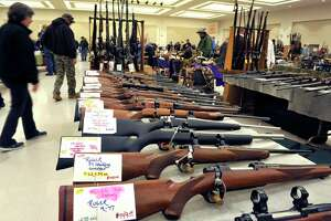 Visitors look over the different firearms for sale at the Arms Fair at the Saratoga Springs City Center on Sunday, Oct. 18, 2015, in Saratoga Spings, N.Y. City Council on Friday banned gun shows at the City Center. (Paul Buckowski / Times Union archive)