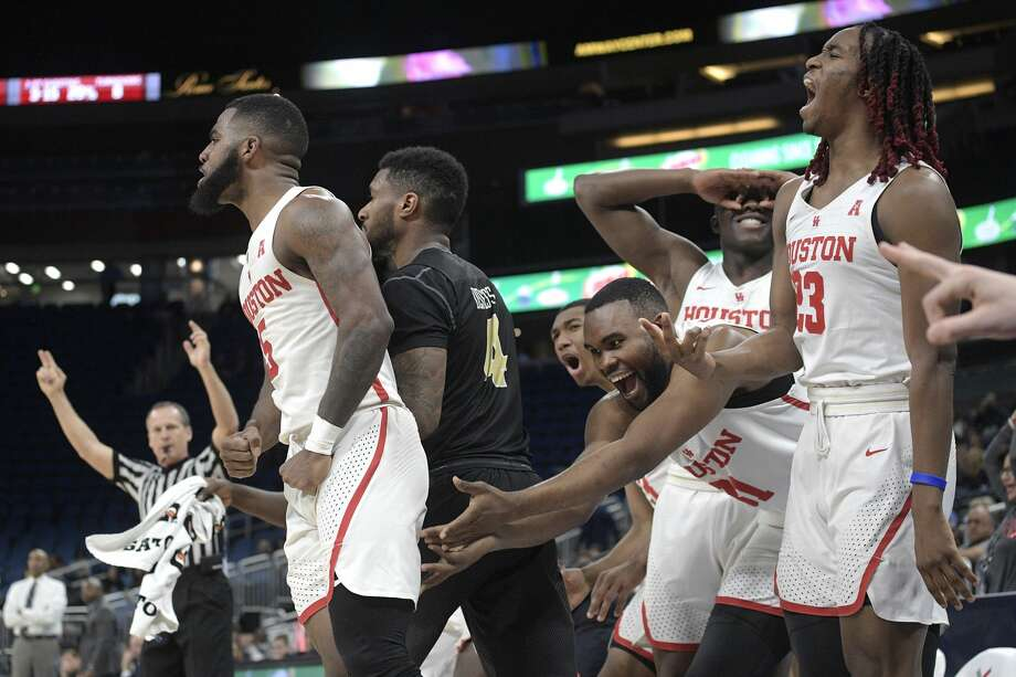 Teammates on the bench react after Houston guard Corey Davis Jr. (5) made a 3-pointer in front of Central Florida guard Ceasar DeJesus (4) during the second half of an NCAA college basketball game in the quarterfinals of the American Athletic Conference tournament, Friday, March 9, 2018, in Orlando, Fla. Houston won 84-56. (AP Photo/Phelan M. Ebenhack) Photo: Phelan M. Ebenhack/Associated Press