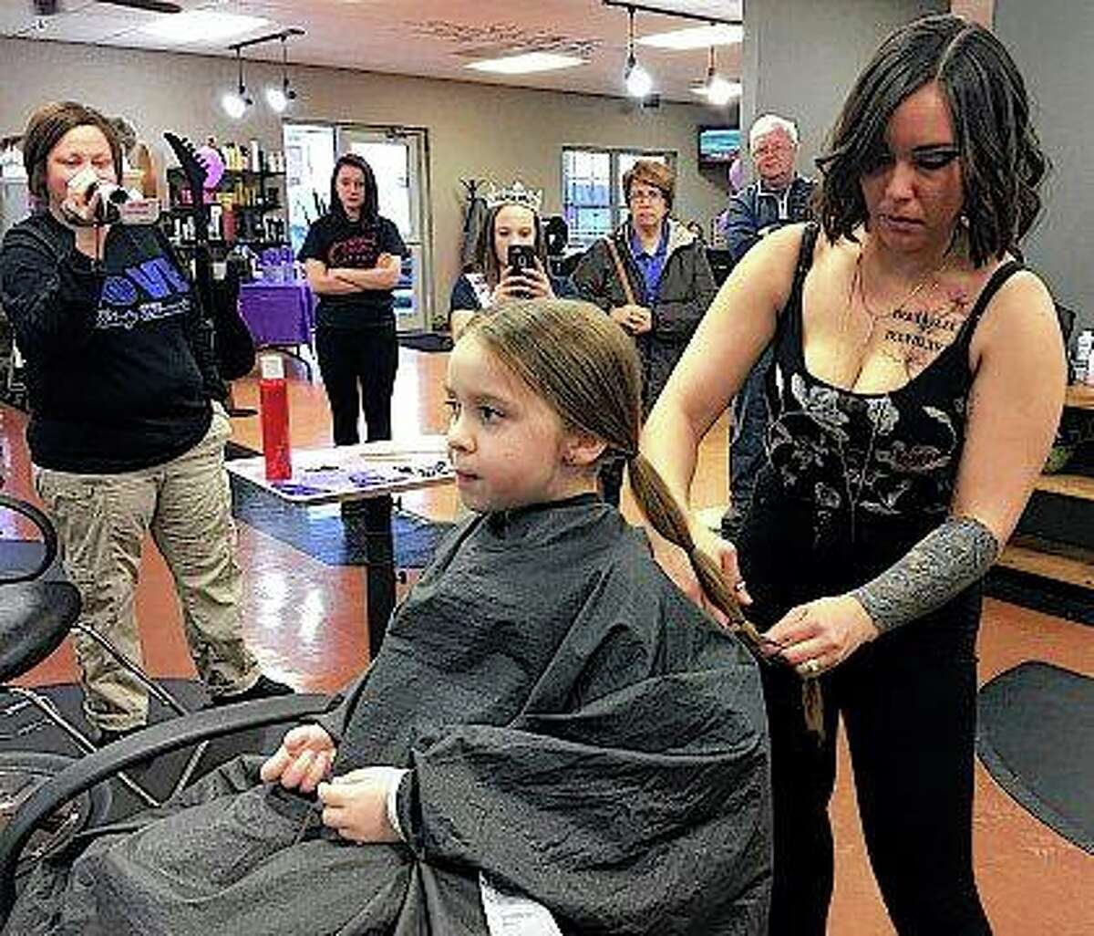 Montana Schmidt, a stylist at Kevin & Co., cuts the hair of Sophia Wright at the salon in Danville as part of Sophia's donation to Pantene's Beautiful Lengths program, which provides free wigs to cancer patients. Sophia inspired at least eight other children and adults to make a hair donation.