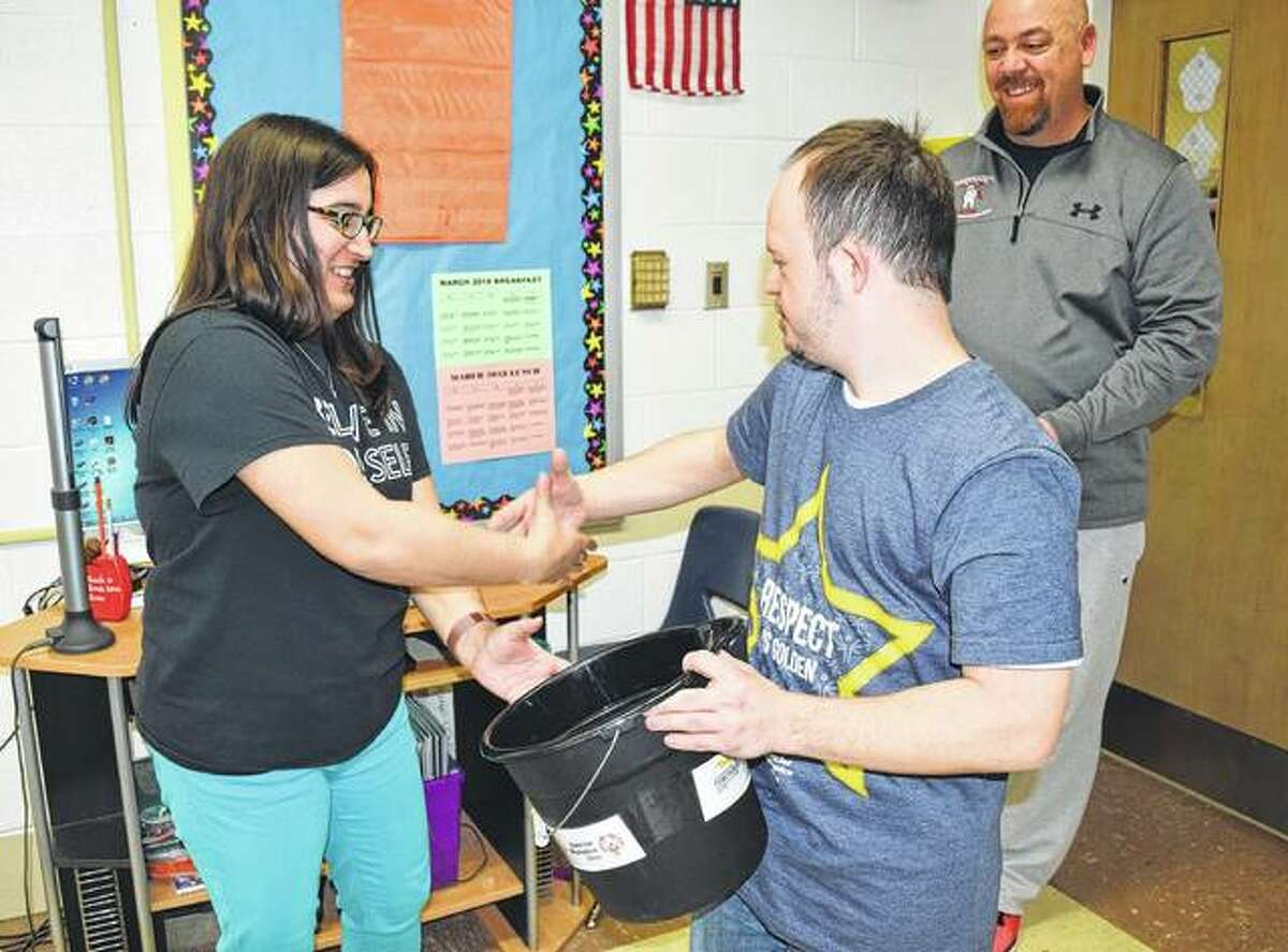 James Foster, a global messenger for Special Olympics, gives a bucket to third grade teacher Raquel Romero Friday to collect pennies during the Meredosia-Chambersburg penny wars to raise money for the Special Olympics.
