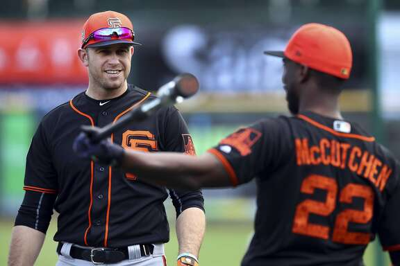San Francisco Giants' Evan Longoria, left, speaks with Andrew McCutchen (22) during a spring training baseball practice on Monday, Feb. 19, 2018 in Scottsdale, Ariz. (AP Photo/Ben Margot)