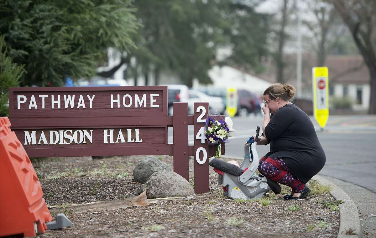 A woman who declined to give her name cries after placing flowers at a sign at the Veterans Home of California, the morning after a hostage situation in Yountville, Calif., on Saturday, March 10, 2018. A daylong siege at The Pathway Home ended Friday evening with the discovery of four bodies, including the gunman, identified as Albert Wong, a former Army rifleman who served a year in Afghanistan in 2011-2012. (AP Photo/Josh Edelson)