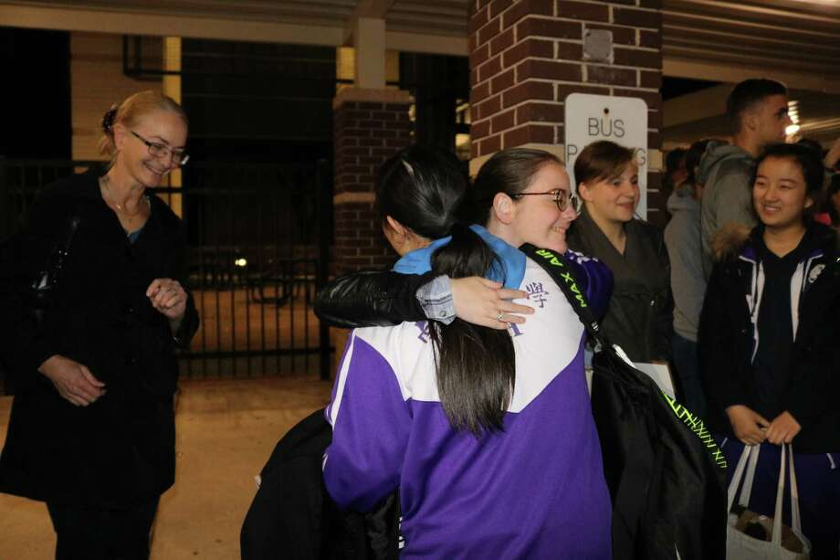 La Porte High School student Christina Longoria gives a welcoming hug to her Nankai High School buddy, Li Xin,  as the visitors get off the bus from the airport.  At left is Christina's mother, Elizabeth Baker. At right are LPHS students Marlo Schatz and her buddy, Liu Changyu.  The 24 Nankai High School students and their two teachers arrived in La Porte on Jan. 29.
