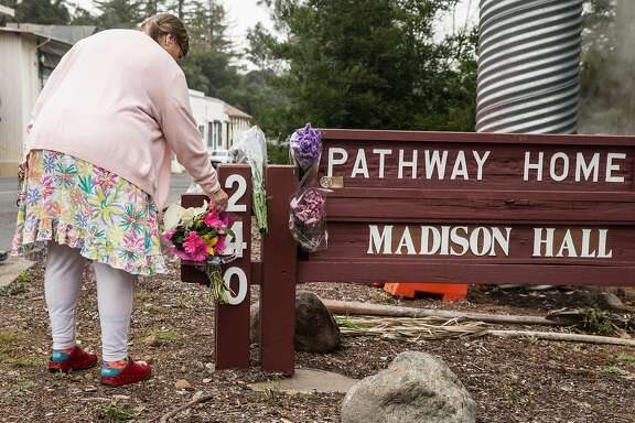 Yountville Veterans Home Member Helper Sandra Wood Ford leaves a flower in memorial following the deadly shooting of three female Pathway Home employees by a former resident at Yountville Veterans Home of California Saturday, March 10, 2018 in Yountville, Calif.