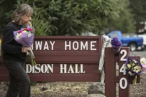 A woman leaves a bouquet of flowers in memorial following the deadly shooting of three female Pathway Home employees by a former resident at Yountville Veterans Home of California Saturday, March 10, 2018 in Yountville, Calif.