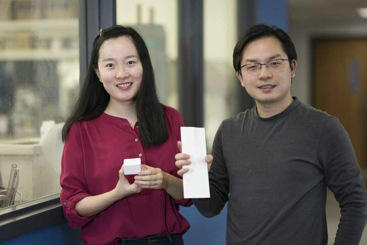 Tian Li, left, and Liangbing Hu hold pieces of nanowood, a strong, lightweight material that serves as an effective insulator. (Hua Xie/University of Maryland)