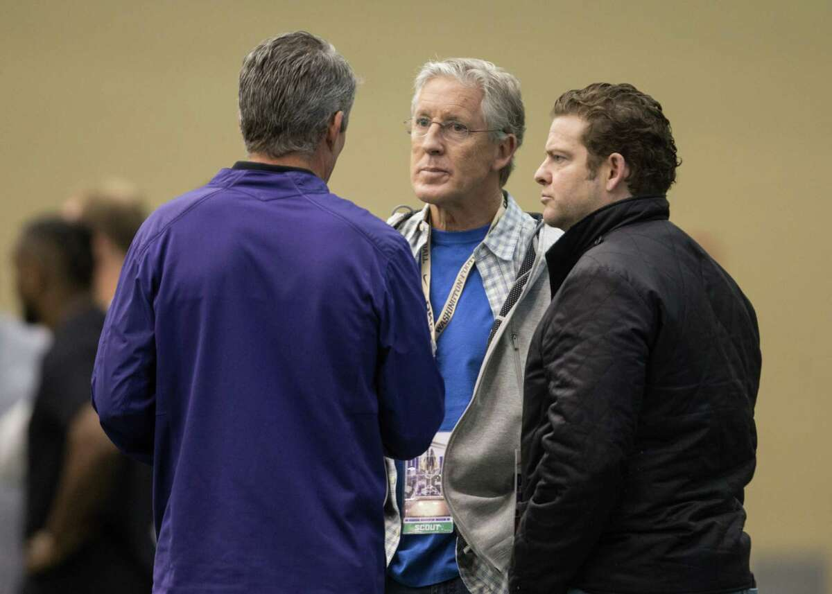 Seahawks head coach Pete Carroll and Seahawks GM John Schneider talk with UW head coach Chris Peterson during UW's Pro Day on Saturday, March 10, 2018.