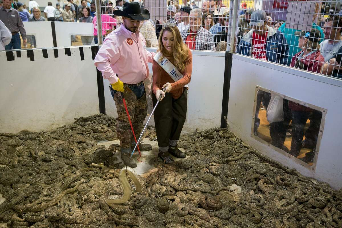 """Travis Gardner assists """"Miss Texas"""" Margana Wood as she makes her way through a pit of rattlesnakes during the Sweetwater Rattlesnake Roundup at Nolan County Coliseum on March 10, 2018 in Sweetwater, Texas."""