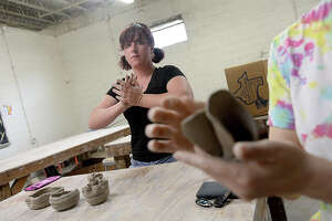 Calley Sledge flattens a piece of clay as she watches the work of a fellow student on the beginning day of the 5-week adult clay class at The Art Studio, Inc. Ceramics artist and instructor Greg Busceme is leading the course, which will ultimately conclude with students firing and glazing their pieces. Photo taken Saturday, March 10, 2018 Kim Brent/The Enterprise