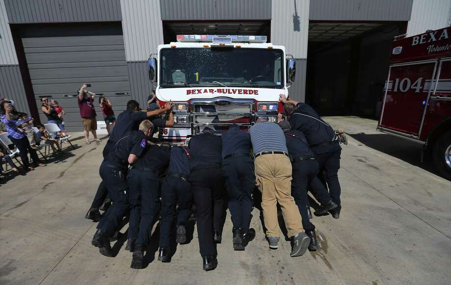 Firefighters with the Bexar-Bulverde Volunteer Fire Department collectively gather to move Engine No. 103 into the station bay as they officially put in service its two new fire engines with a traditional push-in ceremony, at the fire station near Johnson High School on Saturday, Mar. 10, 2018. Before motorized vehicles, it was difficult to back the horse-drawn engines into the garage bays so they were pushed in. Today, firefighters still honor that tradition. The two new engines replace older fire trucks with new state of the art equipment and giving the station more capability in the ever growing area around Stone Oak. (Kin Man Hui/San Antonio Express-News) Photo: Kin Man Hui, Staff / San Antonio Express-News / ©2018 San Antonio Express-News