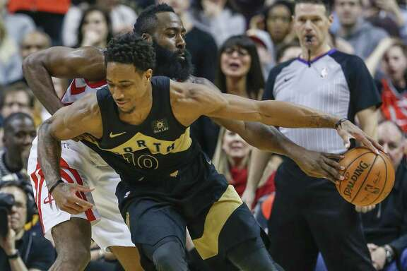 Rockets guard James Harden (rear) knocks the ball from Raptors guard DeMar DeRozan in the second half Friday in Toronto. The two grew up as friends and teammates — as well as rivals.