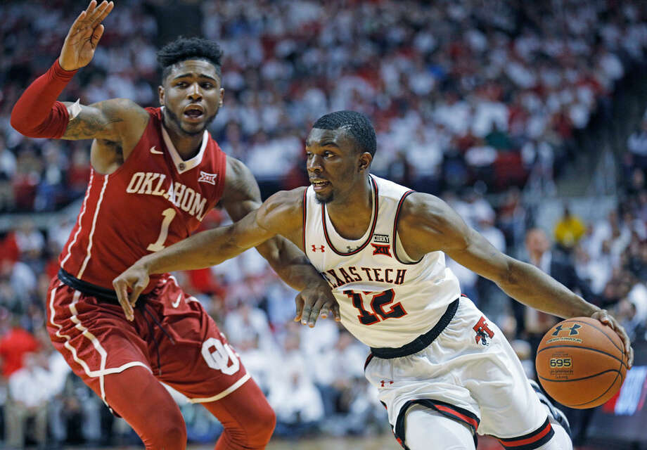 In this Feb. 13, 2018, file photo, Texas Tech's Keenan Evans (12) lays up the ball around Oklahoma's Christian James (1) during an NCAA basketball game, in Lubbock, Texas. AP Photo/Brad Tollefson.