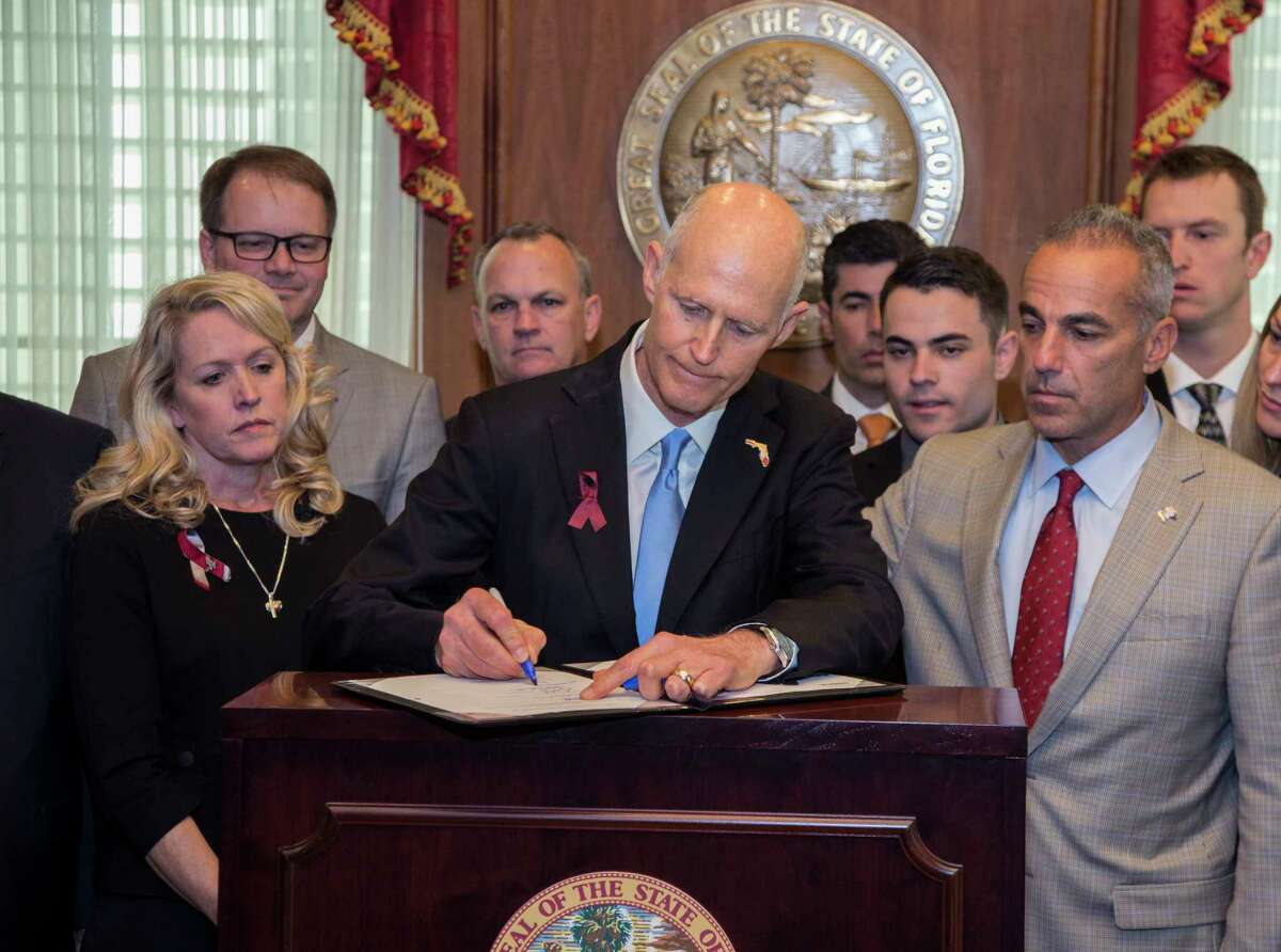 CORRECTS ID OF WOMAN TO GENA HOYER INSTEAD OF JENNIFER MONTALTO - Florida Gov. Rick Scott signs the Marjory Stoneman Douglas Public Safety Act in the governor's office at the Florida State Capitol in Tallahassee, Fla., Friday, March 9, 2018. Scott is flanked by victims' parents Gena Hoyer, left, Ryan Petty, second from left, Andrew Pollack, right, and his son Hunter Pollack, second from right. (AP Photo/Mark Wallheiser)