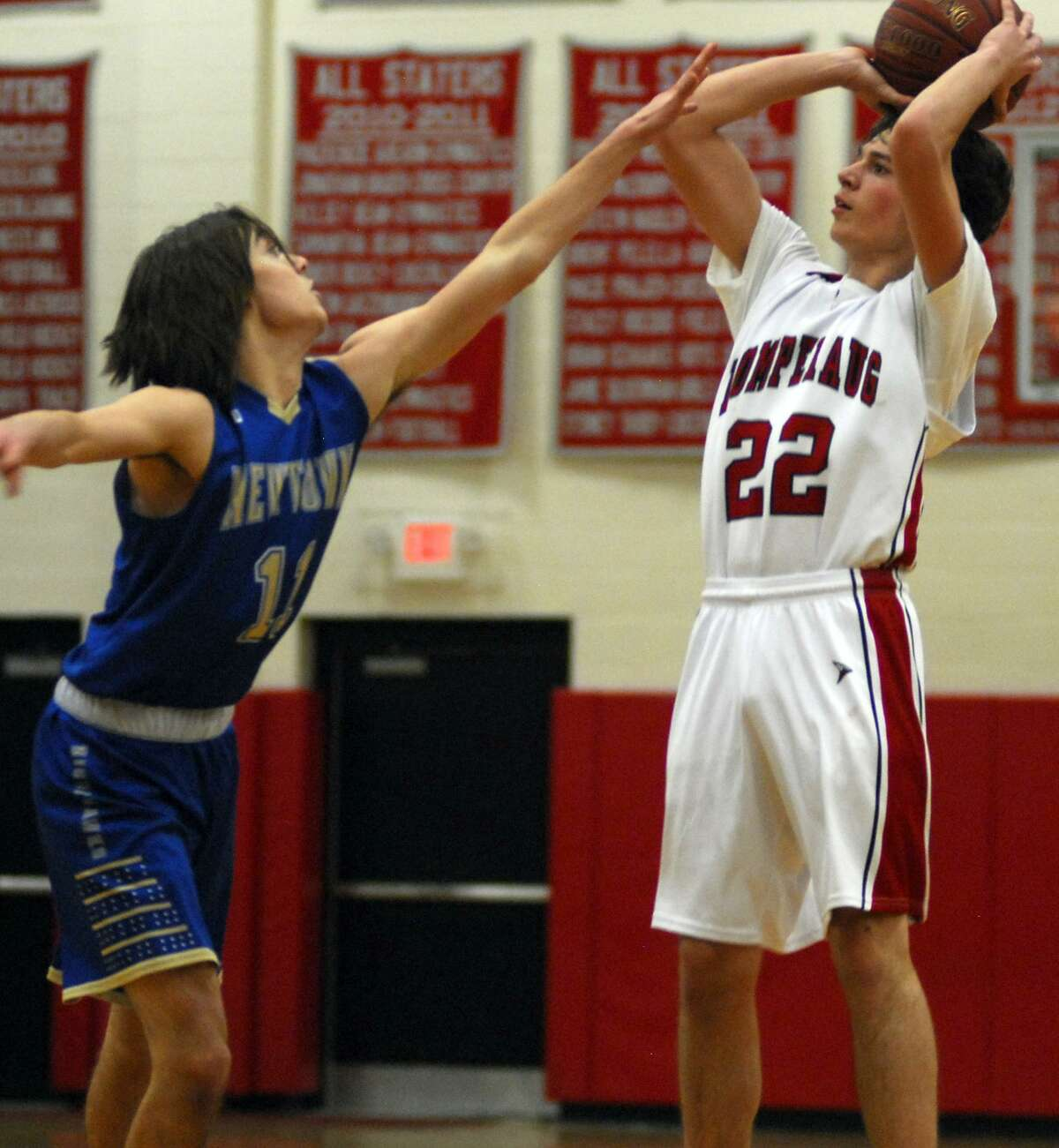Pomperaug's Mario Paniccia, right, gets a shot over a Newtown defender during a game Saturday night.