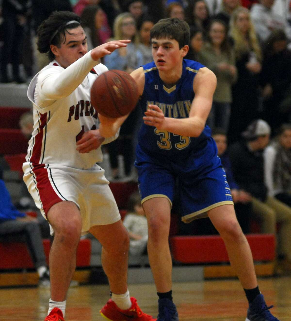Robert Disibio of Newtown, right and Will McDonald of Pomperaug fight for a loose ball during a game Saturday night.