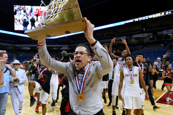 Memorial coach Kenneth Coleman hoists the trophy after the Titans defeated Northwest in the class 5A state final at the Alamodome in San Antonio on Saturday afternoon.   Photo taken Saturday 3/10/18 Ryan Pelham/The Enterprise